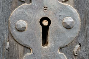 Keyhole of an old wooden door.