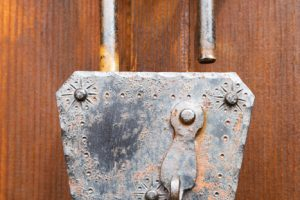 Old rusted and corroded padlock hanging open in a door through two ring handles, close up view