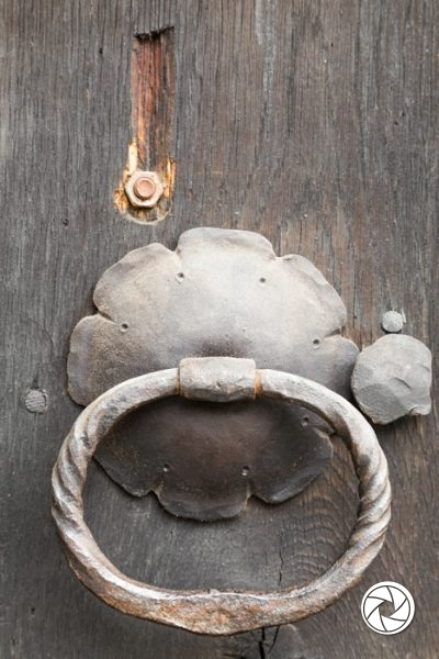 Old cast iron ring handles and escutcheon on an old weather wooden door in a close up view
